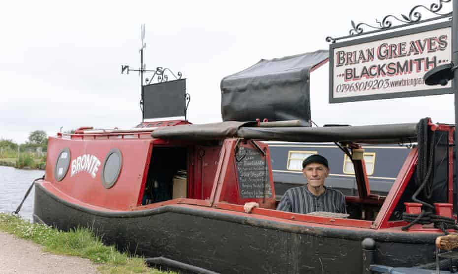 Brain Greaves on board his red canalboat with his business sign on top
