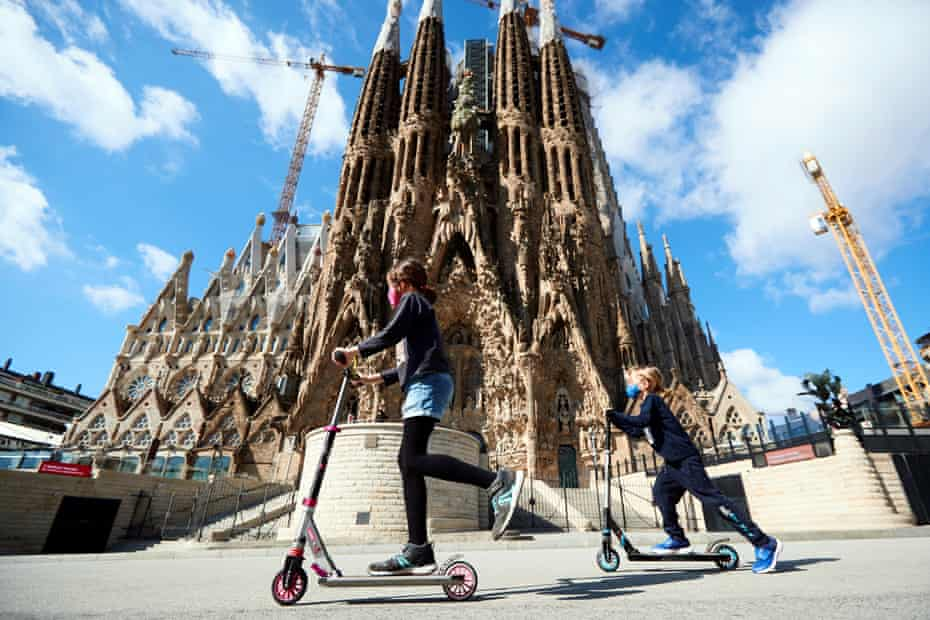 Two girls play in front of the Sagrada Familia in Barcelona