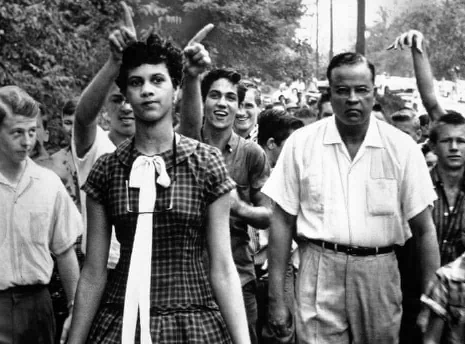 Dorothy Counts, 15, the first black student to attend Harding High School in Charlotte, North Carolina, is followed from school by shouting white students on Sept. 5, 1957. Dr. Edwin Tompkins, a family friend, escorted her. (AP Photo/Douglas Martin)