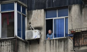 A man looks out of the window at a residential compound in Wuhan