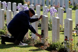 A man places a flower on a tomb in Bayeux