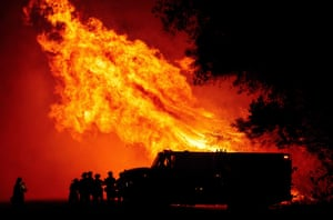 Butte county firefighters watch as flames tower over their truck during the Bear fire in Oroville, California