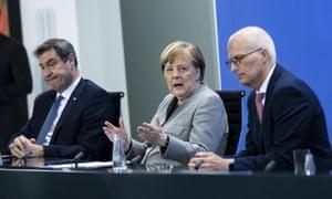 Angela Merkel, centre, with Bavaria's premier, Markus Söder, left, and Peter Tschentscher, first mayor of Hamburg, at a press briefing