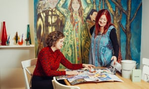 Sophie Heawood sitting at a table doing her collage with Lynne Franks standing and looking at her work, at Lynne's retreat workshot in Somerset.
