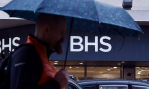 A man with an umbrella outside a branch of BHS