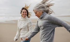 One younger and one older woman run together on the beach