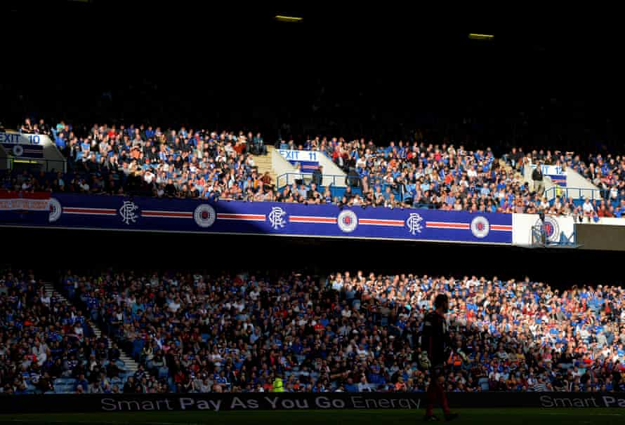 Rangers fans watching their team in the early evening sunlight at Ibrox Stadium, Glasgow.