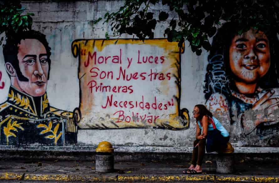 A woman sits next to a mural depicting Latin American liberator Simon Bolivar and one of his quotes, 'Morality and Enlightenment are our prime necessities', in front of a polling station in the Caracas municipality of Sucre