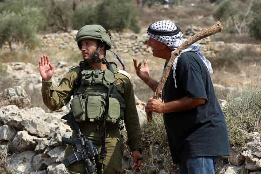 An Israeli soldier with a Palestinian farmer who is waiting to reach a farm to harvest olives, in Yetma, the West Bank.