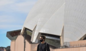 A pedestrian is seen wearing a face mask in front of the Sydney Opera House in Sydney
