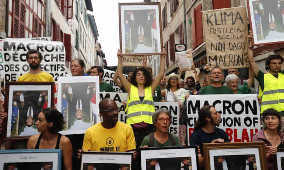 Protesters in Bayonne hold upside-down portraits of the French president, Emmanuel Macron.