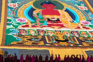 Tibetan Buddhist monks show the thangka to the worshippers