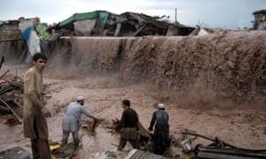 Residents survey the damage after flash floods washed away shops and homes on the outskirts of Peshawar.