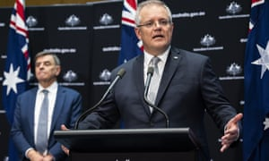 Australian Prime Minister Scott Morrison, flanked by Australia's chief medical officer Brendan Murphy, speaks at a press conference on Friday.