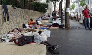 Migrants sleep on mattresses on the pavement in a makeshift camp in Paris.
