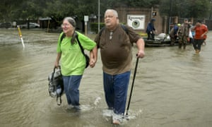 Margie David and her husband David Emswiler are rescued by volunteers on a boat from their flooded house in north-west Houston.