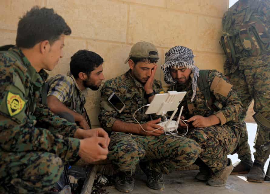 Members of the Syrian Democratic Forces monitor their drone in Nazlat Shahada, a district in Raqqa, on 16 August