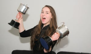 Young teenage girl holding silver cups school trophies.