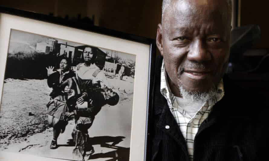 Sam Nzima poses with his famous photograph showing Hector Pieterson being carried after being shot dead by police during the 1976 Soweto uprising