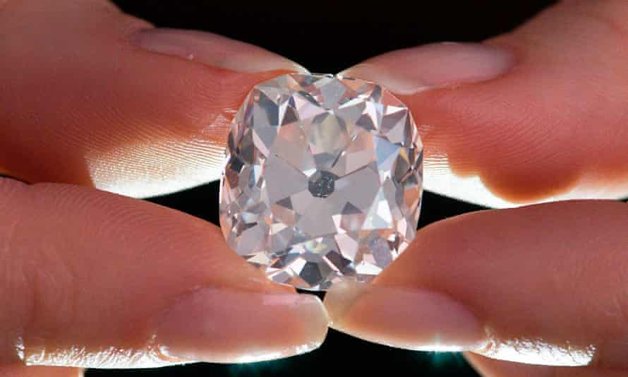 A member of Sotheby's staff poses holding a 26.27 carat, cushion-shaped, white diamond, for sale at Sotheby's auction house