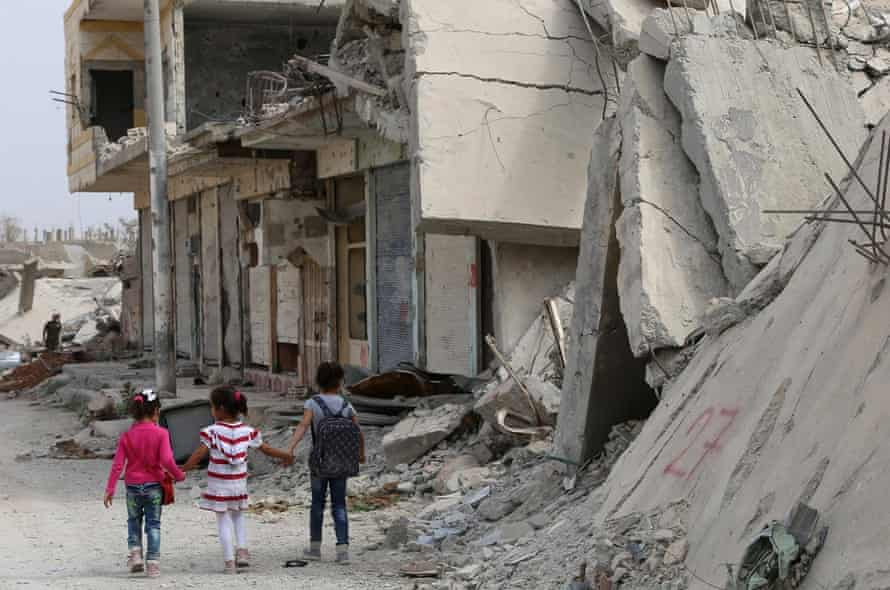 Syrian children walk past debris while heading to school on the second day of the new school year on 6 October 2015 in the Syrian Kurdish town of Kobane