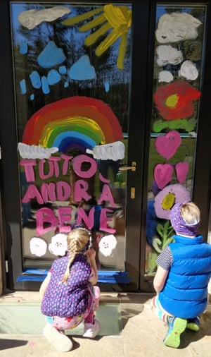 "Children painting a door with the ""andrà tutto bene"" slogan"
