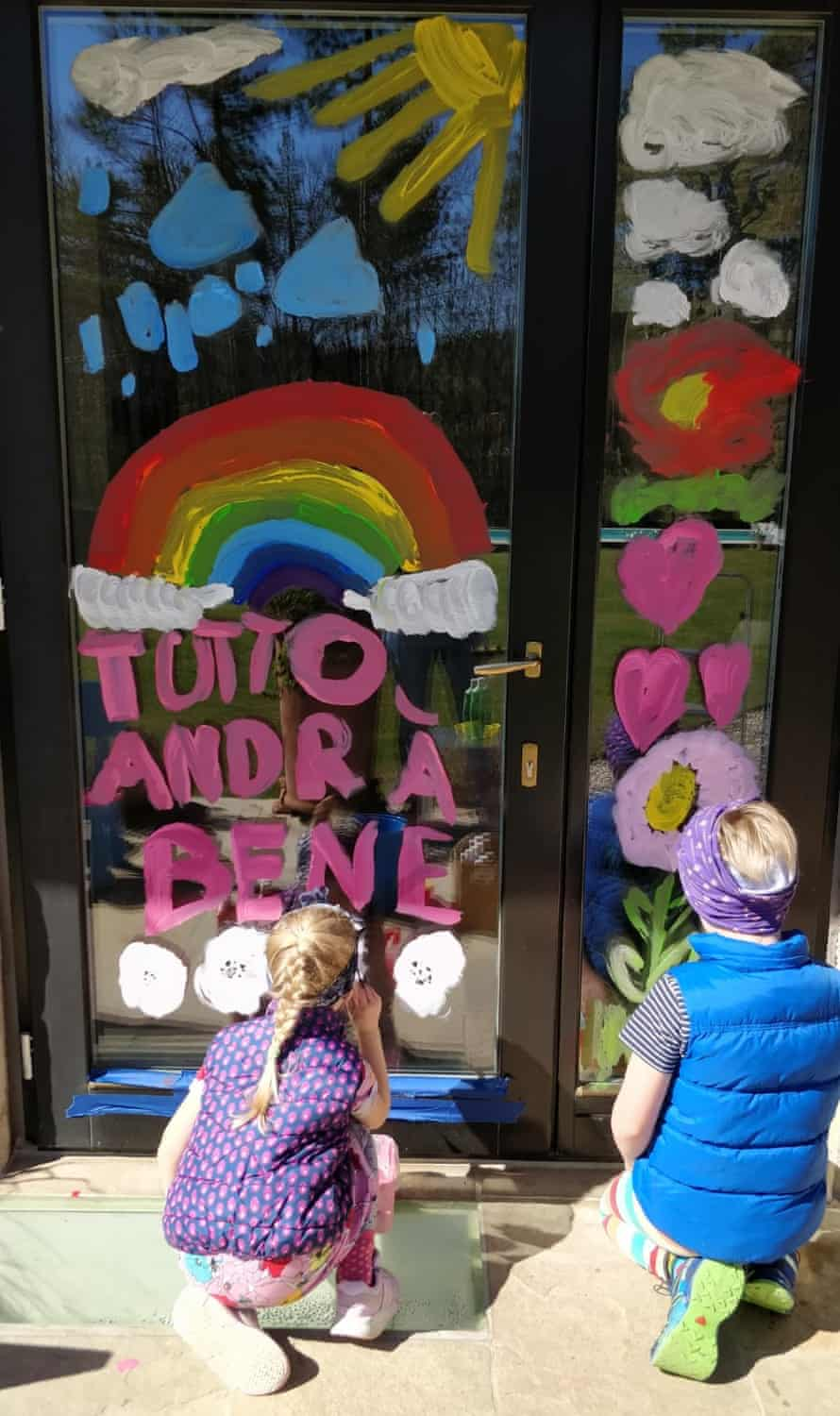"""Children painting a door with the """"andrà tutto bene"""" slogan"""