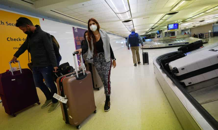 Travellers wear face coverings as they wheel baggage from a carousel in the main terminal of Denver international airport
