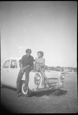 """'This is my oldest brother, Stephen, and my sister Lois sitting on the bonnet of our dad's first car. It was a Ford Prefect. We were all so proud. When dad would drive the car, mum used to say: """"Slow down Huey! Slow down!"""" But the kids used to run beside the car and they would outrun it because dad would drive it so slow! We thought we were rich blackfellas when he bought that car.' – Dallas Phillips."""