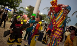 A clown points a toy machine gun at another clown during celebrations on the International Day of the Clown in Cancun December 10, 2012. REUTERS/Victor Ruiz Garcia (MEXICO - Tags: SOCIETY)