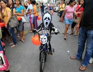 A school boy wearing a mask and a costume arrives on a bicycle before the start of a Halloween Parade along a street in Manila, Philippines