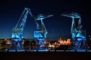 Giant port cranes are illuminated in blue in Szczecin, Poland