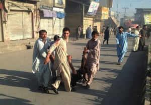 Pakistani residents carry an injured man after twin blasts at a market in Parachinar.