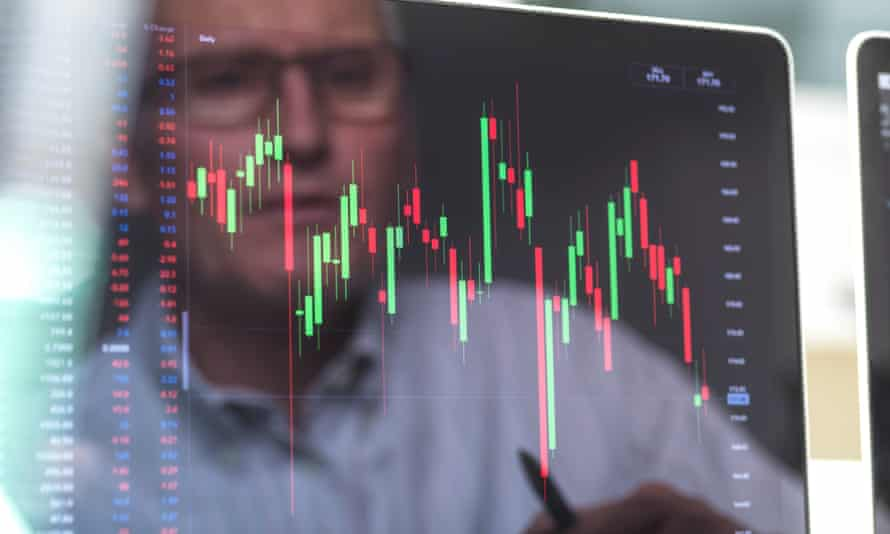 Reflection of a stock trader viewing the performance of a company share price on screen<br>GettyImages-1208356039