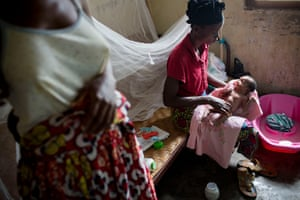 Itunga washes her newborn granddaughter as her mother watches at a health centre near Isangi