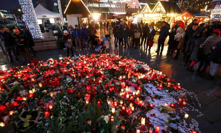 Flowers and candles are placed at the Christmas market at Breitscheid square in Berlin following an attack by a truck which ploughed through a crowd at the market on Monday night