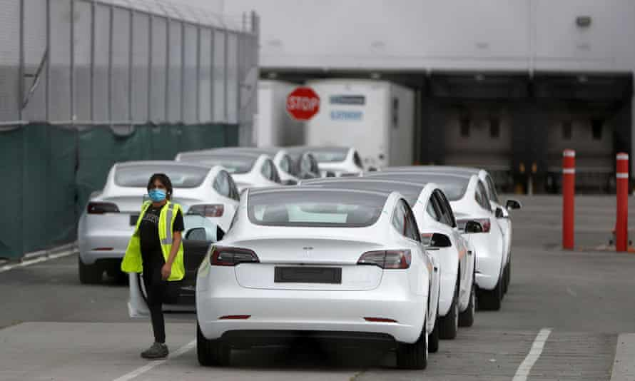 A worker exits a Tesla vehicle at the company's primary factory in Fremont, California, on 11 May.