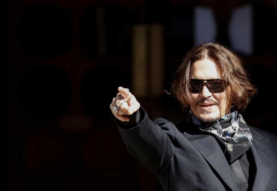 Johnny Depp gestures as he arrives at the Royal Courts of Justice in London