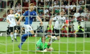 Timo Werner of Germany shoots pastg Estonia's Madis Vihmann and keeper Sergei Lepmets to score his team's seventh goal.