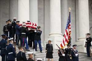 The flag-draped casket of former pesident George HW Bush is carried by a joint services military honour guard from the US Capitol in Washington DC