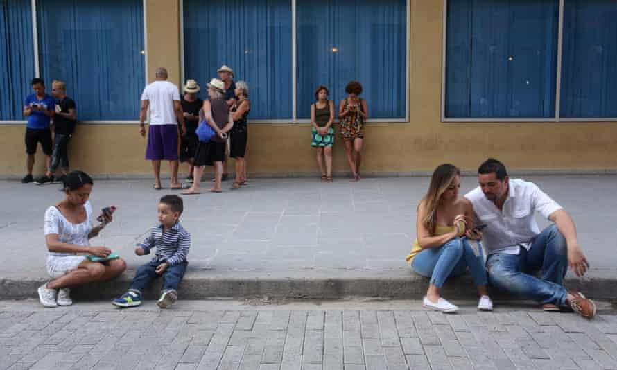 People use public WiFi to connect their devices in a Havana street