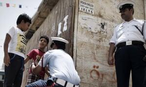 Bahraini police search a boy outside a mosque near Manama.