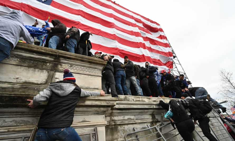 People use barricades as ladders as they storm the US Capitol.
