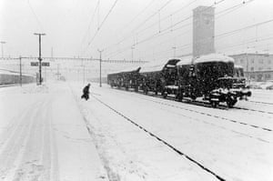 Snow storm on the railway station has stopped a goods train. A railwayman is crossing the tracks.