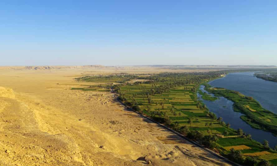 The site of Amarna viewed from the desert cliffs to the north of the city. Cultivation runs along the edge of the Nile, giving way to low desert extending to the cliffs.