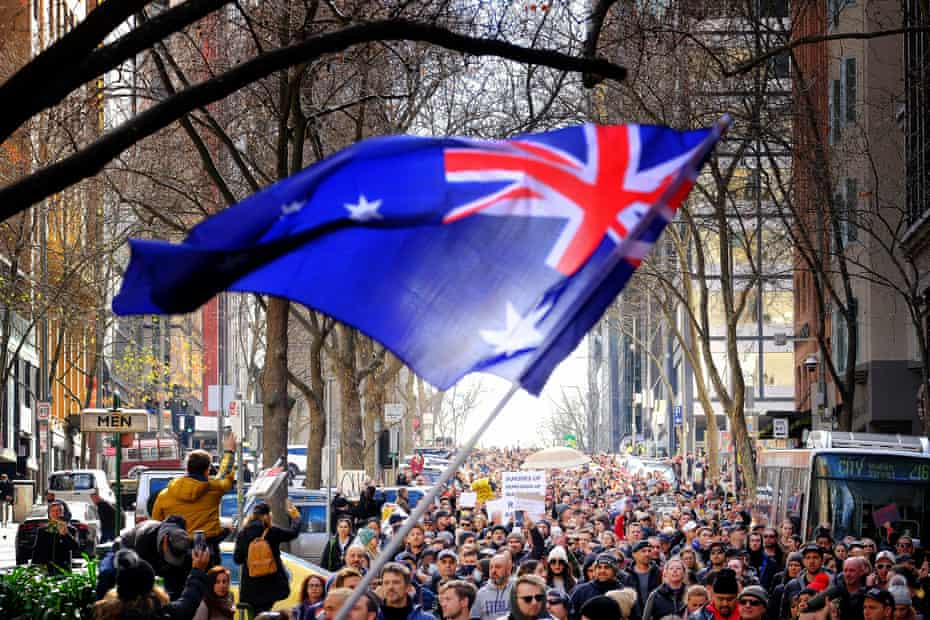 Protesters wave an Australian flag during the anti-lockdown rally in Melbourne on Saturday.