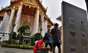 Workers install hand sanitiser dispensers at Wat Suthat Thepwararam temple in Bangkok.