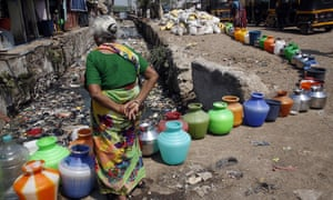 An elderly woman waits to fill pots for filling drinking water at a slum area in Mumbai.
