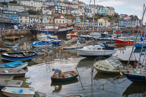 A man makes his way back to the shore after tending to his boat in Brixham, Devon.