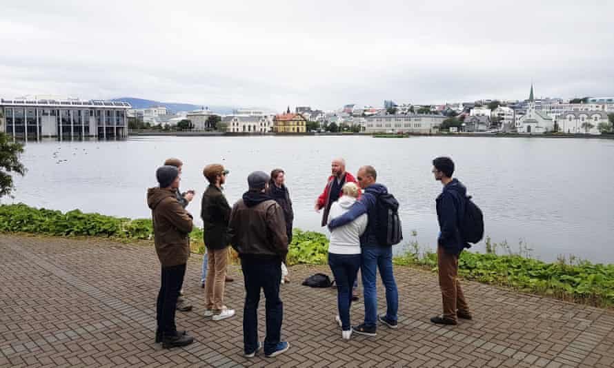 A tour party at the edge of Tjörnin in Reykjavik, and close to the Alþingi, which houses Iceland's parliament.